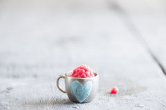 Ripe raspberry in a cup with heart, place for text. Ripe raspberry in a cup on the table Royalty Free Stock Images