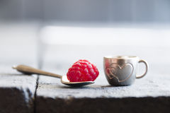 Ripe raspberry in a cup with a heart. Ripe raspberry in a cup on the table Stock Image