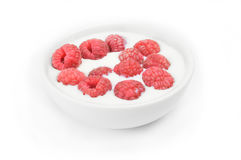 Ripe raspberry into milk in the bowl on white.  Stock Photography