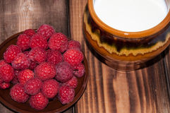 Ripe raspberry and milk jug. On the old wooden table top Royalty Free Stock Image