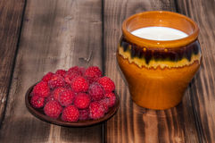 Ripe raspberry and milk jug. On the old wooden table top Stock Photos