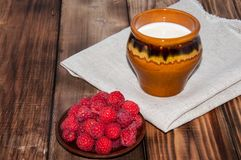 Ripe raspberry and milk jug. On the old wooden table top Stock Images