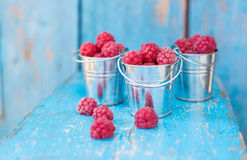 Ripe raspberry in a pail. On a wooden table Royalty Free Stock Photography