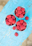 Ripe raspberry in a pail. On a wooden table Royalty Free Stock Photos