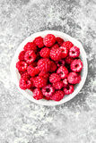 Ripe Raspberry in a white bowl over vintage textuted background,. Close up Stock Image