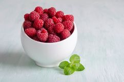 Ripe raspberry in white bowl on the table. Ripe raspberry in white bowl with mint on the table Royalty Free Stock Photo