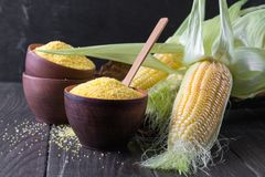 Ripe raw corn cob and green leaves.Corn grits polenta in a  ceramic bowl. Ripe raw corn cob and green leaves on dark wooden background. Corn grits polenta in a Stock Photo