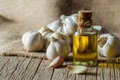 Ripe and raw garlic and garlic oil in glass of bottle on wooden table with burlap sack stock photos