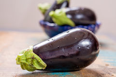 Ripe raw purple eggplants on a wooden background Stock Photography