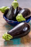 Ripe raw purple eggplants on a wooden background Stock Photos