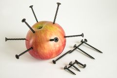 Ripe red Apple with black iron nails. Ripe red Apple with stuck black iron nails and iron formula from the periodic table stock photos