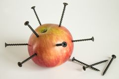 Ripe red Apple with black iron nails. Ripe red Apple with stuck black iron nails and iron formula from the periodic table stock photo