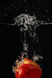 Ripe red apple falling into the water with splash Royalty Free Stock Photography