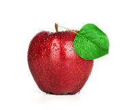 Ripe red apple with green leaf and water drops Royalty Free Stock Photo