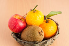 Ripe red apple, kiwi and orange in the basket on plywood backgro Stock Photos