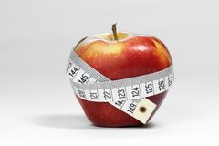 Ripe red apple with a measure tape Stock Images