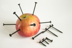 Ripe red Apple with black iron nails. Ripe red Apple with stuck black iron nails and iron formula from the periodic table royalty free stock photography