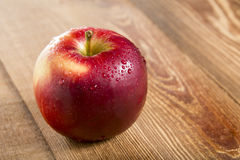 Ripe red apple. On wooden table Royalty Free Stock Photos