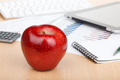 Ripe red apple on workplace Royalty Free Stock Photos
