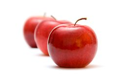 Ripe red apples. Row of three whole ripe red apples receding into distance; isolated on white background Stock Photo