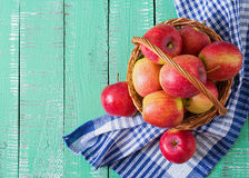 Ripe red apples in a basket on a bright wooden background. Stock Photo