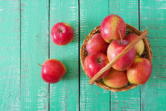 Ripe red apples in a basket on a bright wooden background. Royalty Free Stock Photo