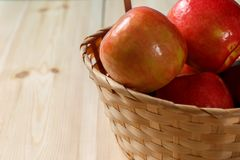 Ripe red apples in a basket. On a bright wooden background royalty free stock photography