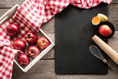 Ripe red apples in birch-box on wooden board with red checkered napkin around and accessories for baking. Top view. Stock Photo