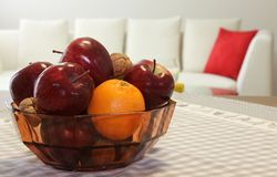 Ripe red apples and fruit in the basket above the table Stock Photo
