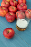 Ripe red apples with a glass of cider blue table  Stock Images