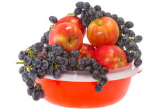Ripe red apples and grapes on a plate Stock Photo