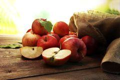 Ripe red apples with leaves on wooden background Royalty Free Stock Image