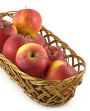 Ripe red apples in long brown wicker basket isolated Stock Photo