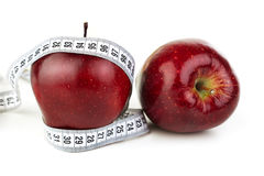 Ripe red apples and a tape measure. Two ripe red apples and a tape measure on a white background Royalty Free Stock Image