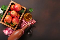 Ripe red apples in wooden box with branch of white flowers, glass and bottle of cider on a rusty background stock photos