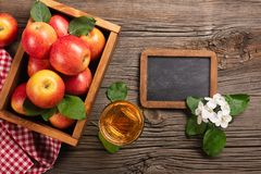 Ripe red apples in wooden box with branch of white flowers, glass of fresh juice and chalk board on a wooden table stock photo