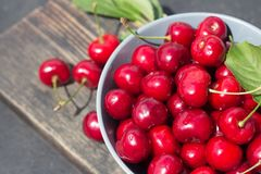 ripe red berries cherries in a round plate on a dark wooden background close-up royalty free stock photography