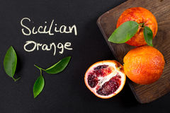 Ripe red blood oranges with cut and green leaves. Isolated on black background Stock Images