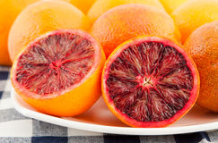 Ripe red blood oranges and slices in the plate Royalty Free Stock Photography