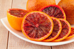Ripe red blood oranges and slices in the plate Stock Photography