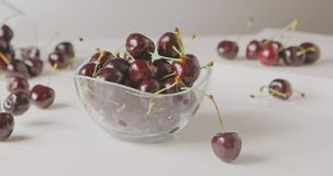 Ripe red cherries with droplets of water fall into a glass bowl on a white table. Soft focus. Slow panoramic motion stock video footage