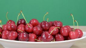 Ripe red cherries. Drops of water on cherries. Green background, slider shot. stock footage