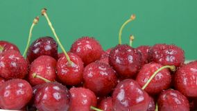 Ripe red cherries. Drops of water on cherries. Green background, slider shot. stock video footage