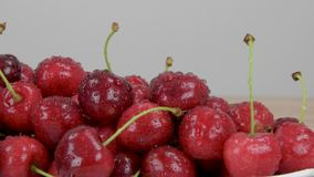 Ripe red cherries. Drops of water on cherries. White background. Slider shot. stock video footage