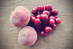 Ripe red cherries and peaches on wooden table, retro filtered Royalty Free Stock Photo