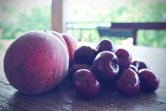 Ripe red cherries and peaches on wooden table, retro filtered Royalty Free Stock Image