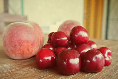 Ripe red cherries and peaches on wooden table, retro filtered Stock Image