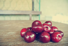 Ripe red cherries on rustic wooden table; retro filtered Stock Photo