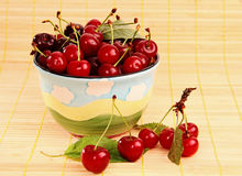 Ripe red cherries on the table and in the cup. Royalty Free Stock Photography