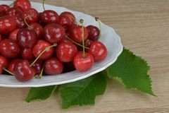 Ripe red cherries on a white plate on a wooden table. Around the green leaves. Stock Images
